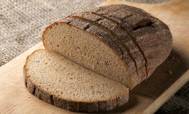 Ein Laib Brot zur Hälfte aufgeschnitten auf einem Holzbrett