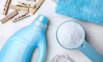 Eine hellblaue Flasche Flüssigwaschmittel, eine Kappe Pulverwaschmittel, ein blaues Handtuch und Holzwäscheklammern