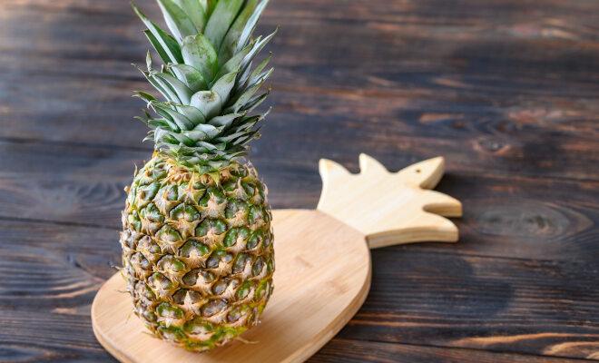 Eine ganze Ananas steht auf einem ananasförmigen Holzbrettchen