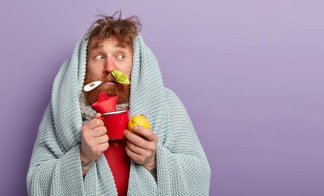 Ein kranker Mann hat ein Thermometer im Mund, ein Taschentuch in der Nase, hält eine Tasse, eine Zitrone und eine Wärmflasche in den Händen und hat eine Wolldecke über dem Kopf