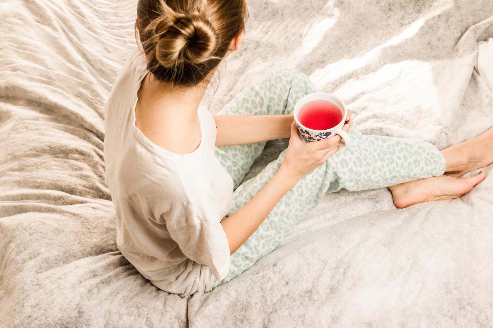 Eine Frau trinkt Tee im Bett
