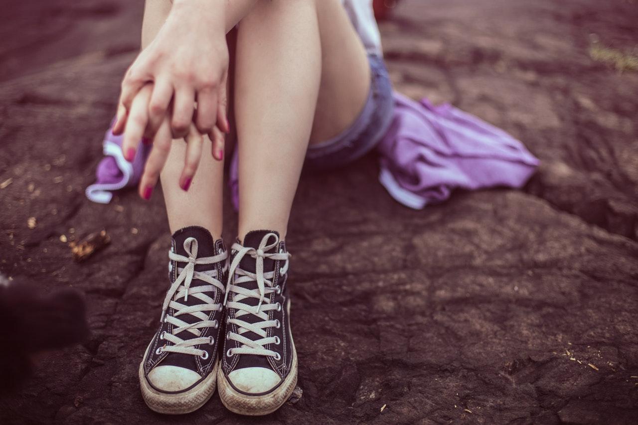 Jugendliche mit All Star Converse sitzt auf einem Baumstamm