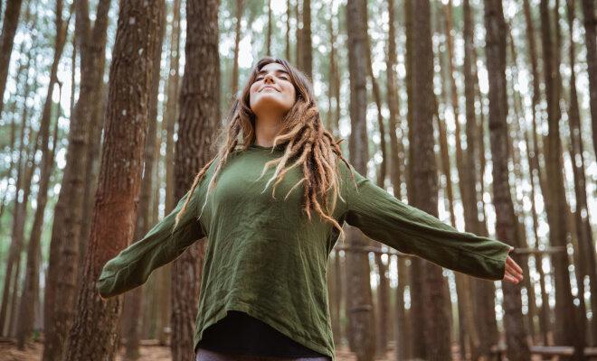 Eine junge Frau steht im Wald, breitet die Arme aus und atmet tief ein