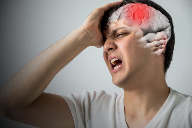 Ein junger Mann hält sich mit einer Hand den schmerzenden Kopf. Eine schematische Darstellung des Gehirns ist mit eingefügt