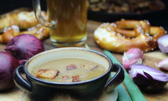 Eine Porzellanschale mit Biersuppe, Laugenbrezen mit Salz, ein gefüllter Bierkrug aus Glas, rote Zwiebeln und Frühlingszwiebeln auf einem Holzuntergrund